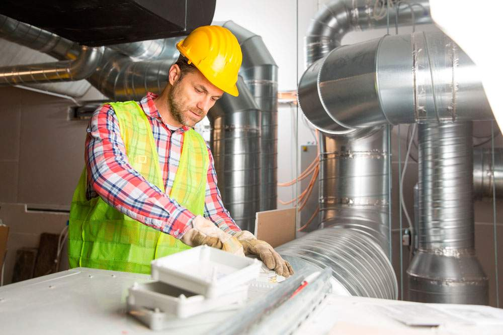 Empresa de instaladores de aire acondicionado en Murcia realizando su labor sobre conducto de A/A