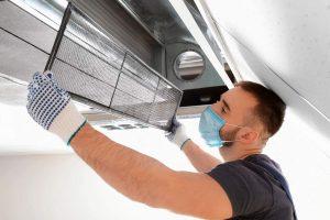 Técnico de aire acondicionado realizando un mantenimiento de climatización en centro educativo