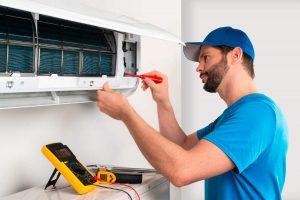 Precio de instalación de aire acondicionado en Murcia e instalador mientras instala aparato interior